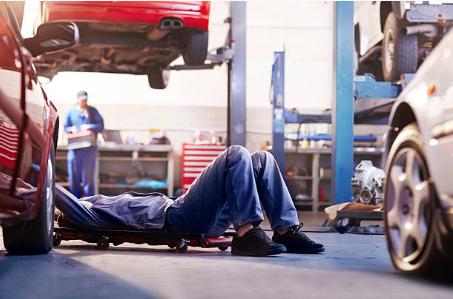 personne allongée qui répare une voiture par en dessous